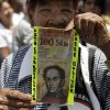 A protester shows a fake bill that reads in Spanish