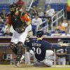 Photo - Milwaukee Brewers' Jonathan Lucroy (20) beats the throw to Miami Marlins catcher Jarrod Saltalamacchia, left, to score on a single hit by Carlos Gomez in the first inning during a baseball game on Sunday, May 25, 2014, in Miami. (AP Photo/Lynne Sladky)