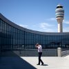 The control tower stands in the background as a passenger paces while on the phone outside the international terminal at Hartsfield-Jackson airport, Friday, April 26, 2013, in Atlanta. Congress easily approved legislation Friday ending furloughs of air traffic controllers that have delayed hundreds of flights daily, infuriating travelers and causing political headaches for lawmakers.(AP Photo/David Goldman)