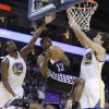 Sacramento Kings\' Tyreke Evans (13) goes up for a shot between Golden State Warriors\' Harrison Barnes, left, and Andrew Bogut (12) during the first half of an NBA basketball game Wednesday, March. 6, 2013, in Oakland, Calif. (AP Photo/Ben Margot)