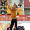Photo - Photographers huddle in the background taking pictures of gold medalist Michel Mulder from the Netherlands as he jumps in celebration during the flower ceremony for the men's 500-meter speedskating race at the Adler Arena Skating Center at the 2014 Winter Olympics, Monday, Feb. 10, 2014, in Sochi, Russia.   (AP Photo/David J. Phillip)