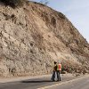 A CalTrans worker and a geologist look at a rock wall where a rockslide closed Carbon Canyon Road near Carbon Canyon Regional Park in Brea, Calif., on Saturday, March 29, 2014 after an earthquake hit Orange County Friday night. More than 100 aftershocks have rattled Orange County south of Los Angeles where a magnitude-5.1 earthquake struck Friday. Despite the relatively minor damage, no injuries have been reported. (AP Photo/The Orange County Register, Ken Steinhardt) MAGS OUT; LOS ANGELES TIMES OUT