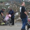 A woman is helped into her wheelchair after being rescued from an apartment building that was demolished by a tornado Wednesday, April 27, 2011 Tuscaloosa, Ala. A wave of severe storms laced with tornadoes strafed the South on Wednesday, killing at least 16 people around the region and splintering buildings across swaths of an Alabama university town. (AP Photo/Caroline Summers)