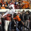 Oklahoma\'s Dejuan Miller (24) catches the ball as Oklahoma State\'s Justin Gilbert (4) tackles him during the Bedlam college football game between the Oklahoma State University Cowboys (OSU) and the University of Oklahoma Sooners (OU) at Boone Pickens Stadium in Stillwater, Okla., Saturday, Dec. 3, 2011. Photo by Sarah Phipps, The Oklahoman