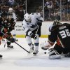 Photo - Anaheim Ducks goalie John Gibson, right, stops a shot by San Jose Sharks' Joe Pavelski, center, during the first period of an NHL hockey game Wednesday, April 9, 2014, in Anaheim, Calif. (AP Photo/Jae C. Hong)