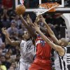 Washington Wizards\' Emeka Okafor (50) works between San Antonio Spurs\' Kawhi Leonard (2) and Tim Duncan, right, during the first half of an NBA basketball game, Saturday, Feb. 2, 2013, in San Antonio. (AP Photo/Eric Gay)