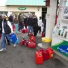 Customers form a queue to fill their gasoline canisters, Wednesday, Oct. 31, 2012, in the Staten Island borough of New York. Sandy, the storm that made landfall Monday, caused multiple fatalities, halted mass transit and cut power to more than 6 million homes and businesses.(AP Photo/ John Minchillo) ORG XMIT: NYJM116
