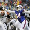 Buffalo Bills defensive end Mario Williams (94) knocks the ball away from Jacksonville Jaguars\' Chad Henne (7) during the first half of an NFL football game on Sunday, Dec. 2, 2012, in Orchard Park, N.Y. Williams recovered the fumble on the play. (AP Photo/Gary Wiepert)