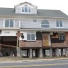 This house in Sea Bright, N.J., shown here on Jan. 15, 2013, is one of the first in the storm-devastated town to be elevated while being rebuilt. The town\'s entire business district was wiped out by Superstorm Sandy (four shops have since re-opened) and 75 percent of residents are still homeless. Yet Sea Bright is determined to rebuild as a debate rages on whether to restore shore communities to their pre-storm condition, or buy out properties in flood-prone areas and depopulate them. (AP Photo/Wayne Parry)