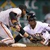 Photo - Pittsburgh Pirates' Starling Marte, right, slides safely around the tag of San Francisco Giants shortstop Brandon Crawford, left, with a stolen base during the third inning of a baseball game in Pittsburgh Monday, May 5, 2014. Giants manager Bruce Bochy called for a replay and the safe call was upheld. (AP Photo/Gene J. Puskar)