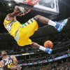 Photo - Denver Nuggets forward Kenneth Faried, top, hangs on the rim after dunking the ball for a basket over Utah Jazz forward Jeremy Evans in the first quarter of an NBA basketball game in Denver on Saturday, April 12, 2014. (AP Photo/David Zalubowski)