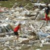 Breanna Bobbitt, 18, and Cameron Bickerstaff, 17 from Ninnekah, help April Winfrey salvage items from part of her manufactured home as residents cleanup following Tuesday\'s deadly tornado on Wednesday, May 25, 2011, in Chickasha, Okla. The home was pulled from concrete piers, split in two and the two halves landed 150 yards apart. Photo by Steve Sisney, The Oklahoman