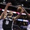 San Antonio Spurs\' Tony Parker, center, of France, is defended by Los Angeles Clippers\' Blake Griffin, left, and Darren Collison during the first half of an NBA basketball game on Monday, Dec. 16, 2013, in Los Angeles. (AP Photo/Jae C. Hong)
