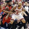 Photo - Chicago Bulls forward Carlos Boozer, right, controls the ball as Toronto Raptors forward Amir Johnson, center, and guard Kyle Lowry guard during the first half of an NBA basketball game in Chicago on Saturday, Dec. 14, 2013. (AP Photo/Nam Y. Huh)