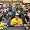 Football player Kai Callins, center in yellow, holds up the