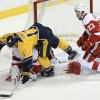 Photo - Nashville Predators forward Nick Spaling (13) falls over Detroit Red Wings goalie Jimmy Howard after stopping a shot by Spaling while being defended by Red Wings defenseman Brian Lashoff (23) in the second period of an NHL hockey game on Monday, Dec. 30, 2013, in Nashville, Tenn. (AP Photo/Mark Zaleski)