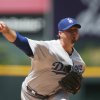Photo - Los Angeles Dodgers starting pitcher Josh Beckett works against the Colorado Rockies in the first inning of a baseball game in Denver, Sunday, July 6, 2014. (AP Photo/David Zalubowski)