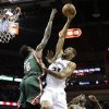 San Antonio Spurs\' Tim Duncan, center, shoots over Milwaukee Bucks\' Larry Sanders (8) as Ekpe Udoh (13) looks on during the first quarter of an NBA basketball game on Wednesday, Dec. 5, 2012, in San Antonio. San Antonio won 99-95. (AP Photo/Eric Gay)