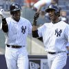 Photo - New York Yankees' Eduardo Nunez, right celebrates with Curtis Granderson after Nunez hit a two-run home run during the fourth inning of an inter-league baseball game against the San Francisco Giants Saturday, Sept. 21, 2013, at Yankee Stadium in New York. (AP Photo/Bill Kostroun)