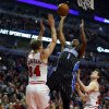 Photo - Orlando Magic guard Doron Lamb (1) shoots between Chicago Bulls forward Mike Dunleavy (34) and guard Jimmer Fredette, right, during the first half of an NBA basketball game Monday, April 14, 2014, in Chicago.  (AP Photo/Jeff Haynes)
