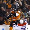 Photo - Philadelphia Flyers' Zac Rinaldo, left, collides with Washington Capitals' Troy Brouwer during the first period of an NHL hockey game, Wednesday, March 5, 2014, in Philadelphia. (AP Photo/Matt Slocum)