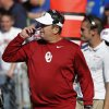 Photo - Oklahoma coach Bob Stoops walks on the sideline during the first half of an NCAA college football game against Kansas in Lawrence, Kan., Saturday, Oct. 19, 2013. (AP Photo/Orlin Wagner)