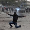 A masked Egyptian protester flashes the victory sign during clashes with riot police, background, near Tahrir Square, Cairo, Egypt, Monday, Jan. 28, 2013. Health and security officials say a protester has been killed in clashes between rock-throwing demonstrators and police near Tahrir Square in central Cairo. The officials say the protester died Monday on the way to the hospital after being shot. (AP Photo/Khalil Hamra)