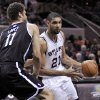 Photo - San Antonio Spurs' Tim Duncan (21) drives around Brooklyn Nets' Brook Lopez during the first half of an NBA basketball game, Monday, Dec. 31, 2012, in San Antonio. (AP Photo/Darren Abate)