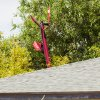 Photo -   The tail of a helicopter sticks up in after it crashed into a backyard between two homes, landing in a tree and knocking off part of a home's roof in Phoenix near the intersection of 19th Street and Roma Wednesday afternoon, May 2, 2012. The fire department said two men were on board when the aircraft went down in a residential area. They were taken to a nearby hospital but appeared to be in stable condition. There was no fire and no injuries on the ground. (AP Photo/The Arizona Republic, Jack Kurtz) MAGS OUT; NO SALES