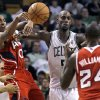 Atlanta Hawks guard Jeff Teague (0) passes off to teammate Marvin Williams (24) against Boston Celtics\' Kevin Garnett, center, during the second quarter of Game 3 of an NBA first-round playoff basketball series, Friday, May 4, 2012, in Boston. (AP Photo/Charles Krupa)