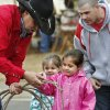 Joe Inman helps Emma Scarborough with the proper placement of her hand on the rope as she learns to lasso. The demonstration is sponsored by the Norman Round-up Club. Behind Emma is her younger sister, Kaitlyn, 3, and their dad, Dan Scarborough. They are from Elgin. Children with their parents endured cold temperatures and intermittent rain to come to the grounds of the Oklahoma History Center on Saturday, March 23, 2013, to participate in the 3rd annual Cowboy Round-up, billed to be a