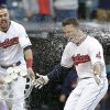 Photo - Cleveland Indians' Lonnie Chisenhall, left, throws cups of water on Zach Walters after Walters hit a game-winning solo home run in the ninth inning of the first baseball game of a doubleheader against the Arizona Diamondbacks, Wednesday, Aug. 13, 2014, in Cleveland. The Indians defeated the Diamondbacks 3-2. (AP Photo/Tony Dejak)