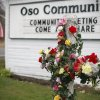 A cross is decorated with flowers in dedication to mudslide victims at the Oso Community Chapel Wednesday, March 26, 2014, in Oso, Wash. (AP Photo/The Herald, Sofia Jaramillo)