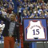 Photo - Former Kansas player and current Miami Heat member Mario Chalmers waves to the crowd as his college jersey is retired during a halftime ceremony at an NCAA college basketball game between Texas and Kansas, Saturday, Feb. 16, 2013, in Lawrence, Kan. (AP Photo/Ed Zurga)