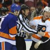 Photo - A referee separates New York Islanders' Matt Carkner (7) and Philadelphia Flyers' Jay Rosehill (37) after fighting in the first period of an NHL hockey game on Monday, Jan. 20, 2014, in Uniondale, N.Y. (AP Photo/Kathy Kmonicek)