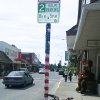 Photo - In this June 12, 2014 photo provided by Fran Hartman, the pole of a street sign is adorned with a pair of yarn flowers in Sitka, Alaska. Hartman, a knitting enthusiast, is yarn-bombing her seaside community by wrapping public poles in knitted casings. Hartman has decorated four poles so far, and plans at least eight more, only she doesn't have the city's official permission. But she's already drawing positive reactions to her private deeds. (AP Photo/Fran Hartman)