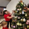 Right: From bottom to top, St. James Catholic School fourth grade students Taylor Bowles, Cecilia Marquez and Miranda Blakley hang rainbow ornaments representing Noah on the Jesse Tree.