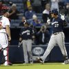 Photo - Milwaukee Brewers' Carlos Gomez (27) and Atlanta Braves catcher Brian McCann (16) exchange words following a home run by Gomez in the first inning of a baseball game Wednesday, Sept. 25, 2013 in Atlanta. (AP Photo/John Bazemore)