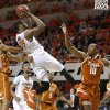 Oklahoma State\'s Marcus Smart (33) goes to the basket between Texas\' Jonathan Holmes (10) and Demarcus Holland during an NCAA college basketball game between the Oklahoma State Cowboys (OSU) and the University of Texas Longhorns at Gallagher-Iba Arena in Stillwater, Okla., Wednesday, Jan. 8, 2014. Oklahoma State won 87-74. Photo by Bryan Terry, The Oklahoman