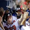 Atlanta Braves\' Elliot Johnson, left, and Jason Heyward, rear right, high-five teammates after scoring off a double by Evan Gattis in the second inning of a baseball game against the Philadelphia Phillies, Thursday, Sept. 26, 2013, in Atlanta. (AP Photo/David Goldman)
