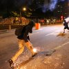 Photo - A masked anti-World Cup demonstrator runs to throw a molotov cocktail at police during a protest demanding better public services and against the money spent on the World Cup soccer tournament near Maracana stadium in Rio de Janeiro, Brazil, Sunday, June 15, 2014. Police clashed with protesters marching toward the stadium ahead of the match between Argentina and Bosnia. (AP Photo/Leo Correa)