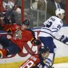 Photo - After slamming into Toronto Maple Leafs' Jerred Smithson (22), Florida Panthers' Dmitry Kulilov (7) is knocked to the ice during the first period of an NHL hockey game in Sunrise, Fla., Tuesday, Feb. 4, 2014. (AP Photo/J Pat Carter)