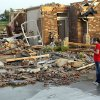 Photo - OKLAHOMA CITY TORNADO DAMAGE /  Ann Powell calls her insurance company while standing in front of what is left of her house at 306 Mounds, just south of Harrah Road and Reno Monday evening after tornados ripped through the area. Powell moved to Oklahoma about a year ago from California.   BY HUGH SCOTT, THE OKLAHOMAN ORG XMIT: KOD