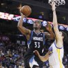 Photo - Minnesota Timberwolves' Dante Cunningham shoots as Golden State Warriors' Klay Thompson defends during the first half of an NBA basketball game, Tuesday, April 9, 2013, in Oakland, Calif. (AP Photo/George Nikitin)