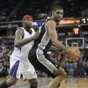 Photo -   San Antonio Spurs forward Tim Duncan, right, goes to the basket against Sacramento Kings center DeMarcus Cousins during the first quarter of an NBA basketball game in Sacramento, Calif., Friday, Nov. 9, 2012. (AP Photo/Rich Pedroncelli)