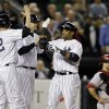 New York Yankees\' Lyle Overbay, left, and Chris Stewart greet Robinson Cano at the plate after they scored on Cano\'s fourth-inning, three-run home run in a baseball game at Yankee Stadium in New York, Tuesday, April 16, 2013. Arizona Diamondbacks catcher Miguel Montero is at far right. (AP Photo/Kathy Willens)