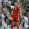Photo - Toronto FC forward Gilberto (9) controls the ball between Sporting Kansas City midfielder Paulo Nagamura (6) and defender Kevin Ellis (4) during the first half of an MLS soccer match in Kansas City, Kan., Friday, May 23, 2014. (AP Photo/Orlin Wagner)