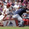 Photo - St. Louis Cardinals' Kolten Wong, left, scores as the throw gets past Atlanta Braves catcher Evan Gattis during the fourth inning of a baseball game on Saturday, May 17, 2014, in St. Louis. (AP Photo/Jeff Roberson)
