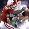 Nebraska\'s Courtney Osborne (12) tries to bring down Oklahoma\'s Trent Ratterree (47) during the Big 12 football championship game between the University of Oklahoma Sooners (OU) and the University of Nebraska Cornhuskers (NU) at Cowboys Stadium on Saturday, Dec. 4, 2010, in Arlington, Texas. Photo by Chris Landsberger, The Oklahoman