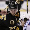 Boston Bruins center Patrice Bergeron (37) eyes the puck on a face-off with Montreal Canadiens center David Desharnais (51) 06during the second period of an NHL hockey game, Monday, March 24, 2014, in Boston. (AP Photo/Charles Krupa)